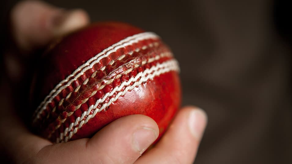 picture of a red cricket ball in the hands of a cricketer