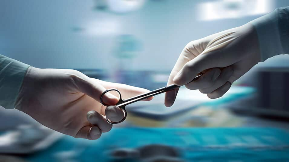 photograph of one hand surgeon passing hemostat or forceps to another hand surgeon during surgery