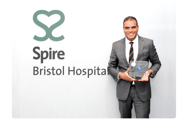 picture of mr raj bhatia with award for the best hand and wrist clinic in the south west of england whilst standing in the spire Bristol hospital