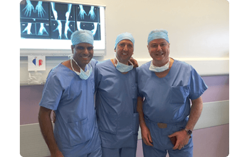 image of raj Bhatia with 2 other surgeons dressed in blue scrubs standing in operating theatre arms wrapped around each other posing for this picture
